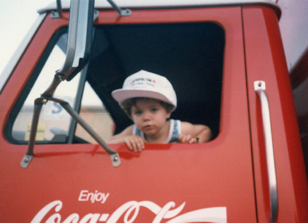 A young, precocious Chris Cottrell hanging out of a Coca-Cola pickup truck